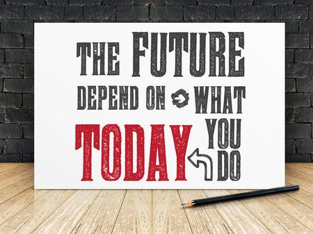 """cotizacion: Cita de la inspiración: """"El futuro depende de lo que hagas hoy"""" en el marco blanco en la pared de ladrillo negro y suelos de madera, tipográfico motivación."""