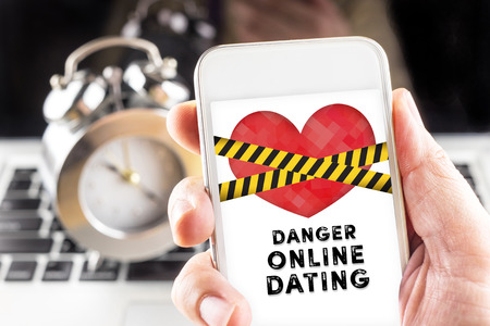 caution tape: Hand holding mobile with caution tape on heart and Danger online dating  on screen with clock and laptop at background, Internet love concept.