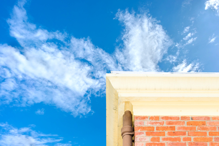 modern architecture: Looking up at brick house with blue sky.