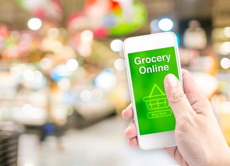 abarrotes: Mano que sostiene móvil con la tienda de comestibles en línea en la pantalla con fondo borroso supermercado, concepto de entrega en línea. Foto de archivo
