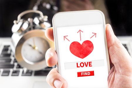 internet love: Hand holding mobile with red heart and find love word on screen with clock and laptop at background, Internet love concept.