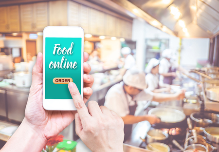 in order: Hand holding mobile with Order food online with blur restaurant background, food online business concept.Leave space for adding your text.