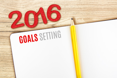 new year: 2016 Goals Setting word on notebook lay on wood table,Template mock up for adding your goal. Stock Photo