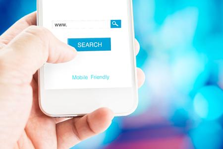 Hand houden van mobiele telefoon met zoekpagina op het scherm met mobiele vriendelijke functie op wazig blauwe achtergrond, Search engine business concept.