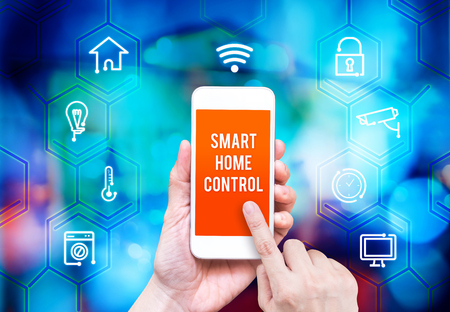 home computer: Hand holding smart phone with home control application with blur home background, Smart home concept.