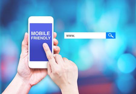 흐린 파란색 배경에 검색 상자와 휴대하기 쉬운 단어로 손 터치 휴대 전화, 디지털 마케팅 비즈니스 개념입니다.