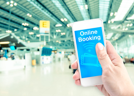Hand holding mobile with online booking with blur airport background, Digital Booking concept. Stock Photo