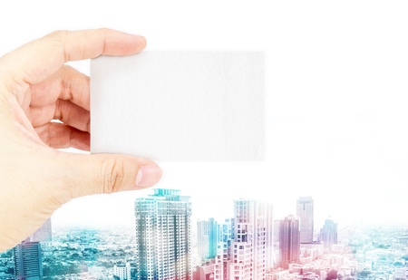 overly: Hand holding blank business card with overly color with cityscape background,Business concept.