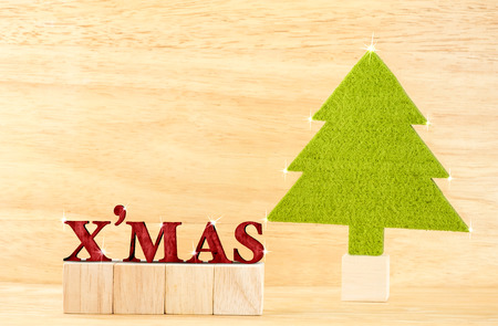cuve: red xmas word with green christmas tree in wooden room,holiday concept. Stock Photo
