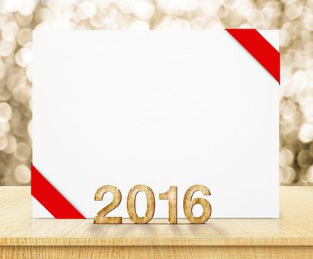 nowy rok: biały plakat z czerwoną wstążką i 2016 roku struktura drewna z musującym złotym bokeh ściany i drewniane tabeli. Zdjęcie Seryjne