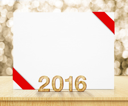 year's eve: white poster with red ribbon and 2016 year wood texture with sparkling gold bokeh wall and wooden table.