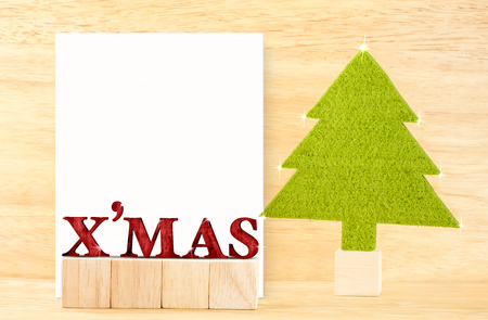 red xmas word and blank postcard with green christmas tree in wooden room,holiday concept, leave space for adding your text. Stock Photo