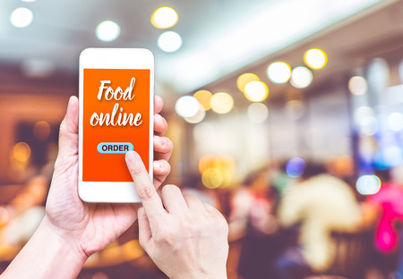 mobile: Hand holding mobile with Order food online with blur restaurant background, food online business concept.Leave space for adding your text.