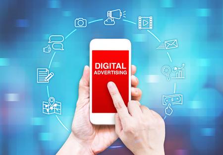 Hand hält Smartphone mit Digital Advertising Wort und Symbol auf blauem Pixel Unschärfe Hintergrund, Digital Marketing concpet. Standard-Bild - 47898743