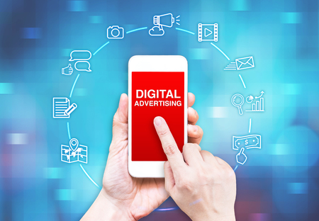 redes de mercadeo: Mano que sostiene teléfono inteligente con la publicidad digital y el icono de la palabra sobre fondo azul desenfoque de píxeles, concpet Marketing Digital.