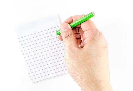 escritura: Mano que sostiene un lápiz de escritura verde en la pista de nota gobernado aislado en el fondo blanco. Foto de archivo