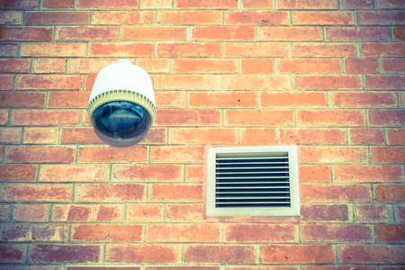 theft prevention: Security camera on orange brick wall. Stock Photo