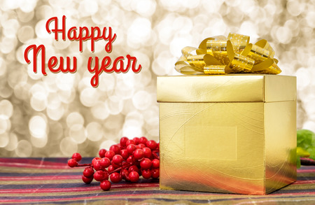 ash berry: Happy new year word with Gold present box and ribbon on table with sparkling gold bokeh light background, Holiday concept.