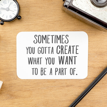 """Inspiration quote : """" Sometime you gotta create what you want to be a part of"""" word on paper at wooden table with clock,camera,pencil ,Motivational typographic."""