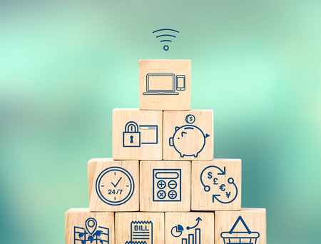 shoppping: Mobile banking feature icon on wood cube pyramid with blur blur background, Digital marketing concept. Stock Photo