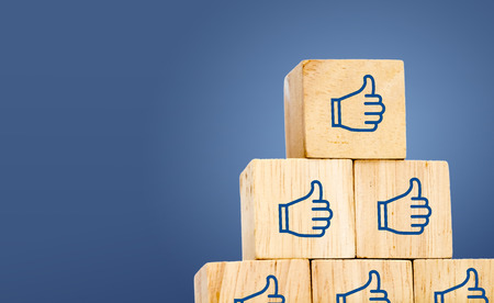 thumb up icon: Thumb up icon on wood cube at dark blue background, leave space for adding text. Stock Photo