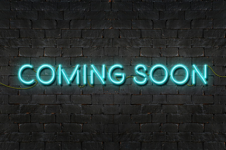 COMING SOON neon sign shining on black brick wall,Business concept.
