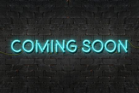 """paredes de ladrillos: """"Muy pronto"""" cartel de neón que brilla en la pared de ladrillo negro, concepto de negocio."""