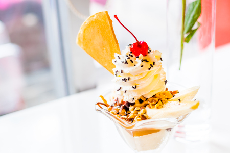 Sundae ice cream on table with rose flower at glass window. Stock Photo