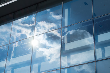 Sun ray and blue sky reflection on window office building, Business concept.