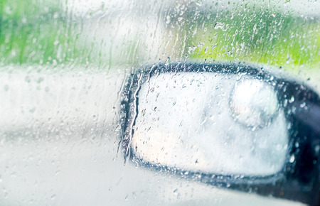 see through: See through car window to side rear-view mirror in raining day.