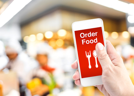 orders: Hand holding mobile with Order food online with blur restaurant background, food online business concept.Leave space for adding your text.