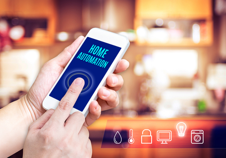 home automation: Hand holding smart phone with home control application with blur home background, Smart home concept.