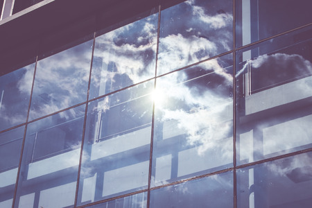 reflection: Sun ray and blue sky reflection on window office building, Business concept,vintage filter.
