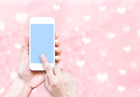 heart background: Hand holding smart phone with black screen on pink pastel heart bokeh background, Leave space for adding your content.
