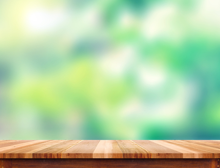 Empty plank brown wood table top with blur green tree background, Template mock up for montage of product. 스톡 콘텐츠