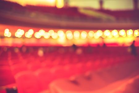 Sfondo sfocato, fila di sedili rosso in teatro con filtro d'epoca.
