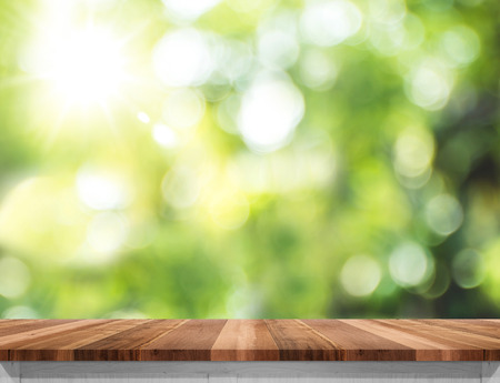 forest products: Empty brown wood table top with sun and blur green tree bokeh background, Template mock up for montage of product. Stock Photo