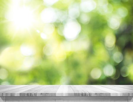 Empty planche blanc table en bois haut flou arbre vert bokeh fond, modèle maquette pour le montage du produit. Banque d'images