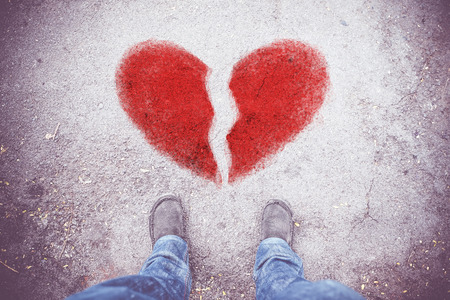 filtro de la vendimia: vista aérea del zapato de tela gris con blue jean de pie con el corazón roto de color rojo en el grunge piso de concreto, el concepto de amor.