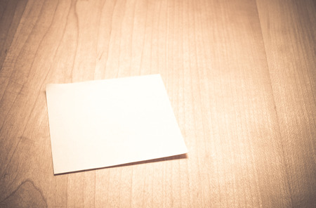 Blank Note paper on wooden table with vintage filter.