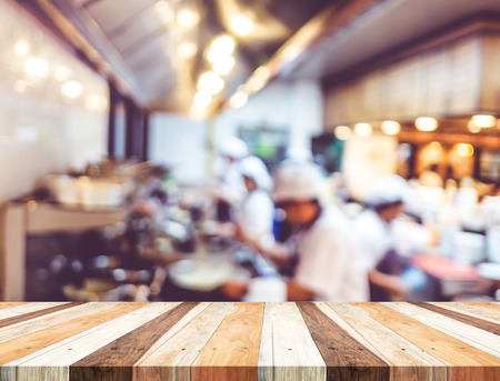 web menu: Empty wood table with blur open cooking restaurant background,Mock up Template for montage of your product. Stock Photo