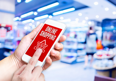 Hand holding mobile phone with Online shopping word with blurred store background,Digital marketing concept. Stock Photo