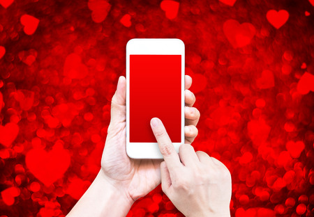 romantic man: Hand holding smart phone with black red screen on red heart bokeh background, Leave space for adding your content.