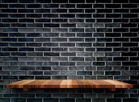 barra de bar: estantes de madera vacíos en la pared de ladrillo negro, maqueta plantilla para la exhibición de productos. Foto de archivo
