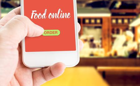 Mano que sostiene móvil con alimentos Orden en línea con el fondo de la falta de definición restaurante, comida concepto de negocio en línea.