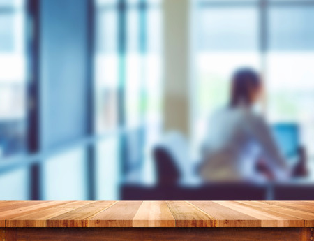 Empty light wood table top with blur office background, Leave space for placement you content,Template mock up for montage of product.