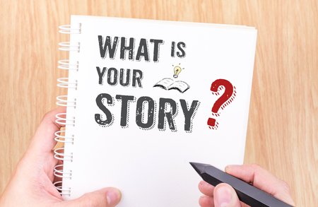 honest: What is your story work on white ring binder notebook with hand holding pencil on wood table,Business concept.