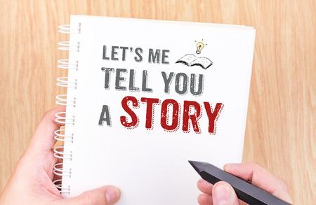 Lassen Sie uns mich Ihnen eine Geschichte erzählen Arbeit auf weißem Ringbuch Notebook mit Hand hält Bleistift auf Holztisch, Geschäftskonzept. Standard-Bild