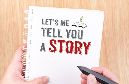 Vamos a que te cuente una historia funcione en el anillo blanco encuadernación portátil con la mano que sostiene un lápiz sobre la mesa de madera, concepto de negocio. Foto de archivo
