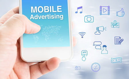 influencer: Hand touch mobile phone with mobile advertising word with feature icon at blurred grey background, Digital marketing business concept. Stock Photo